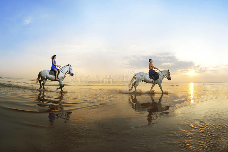 Twee minnaars die op een paard van het overzees bij zonnen galopperen royalty-vrije stock foto's