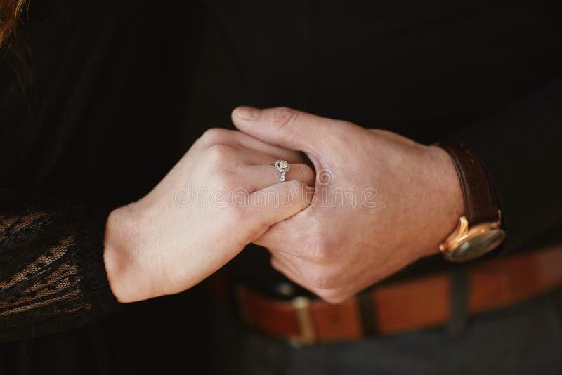 Twee minnaars, een paar, een jongen en een meisje houden handen Het meisje op haar hand is een trouwring Het concept liefde stock fotografie