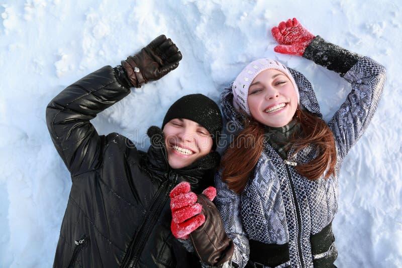Twee minnaarsmensen liggen op sneeuw stock afbeelding