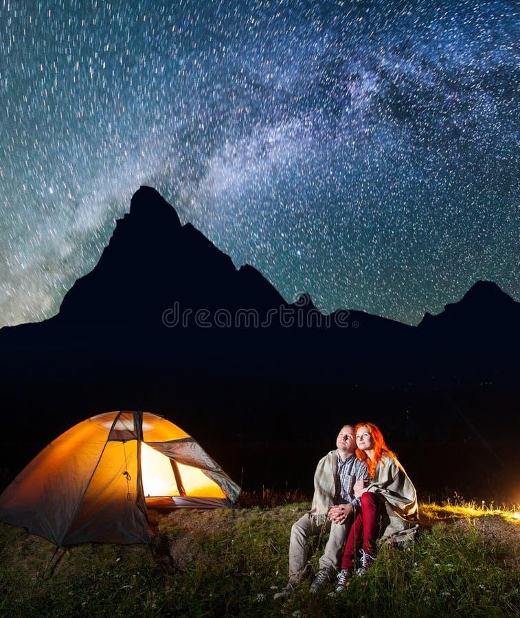 Twee minnaarswandelaars die samen dichtbij kampvuur zitten en glanst kamp bij nacht onder sterren en het kijken aan de sterrige h stock foto's