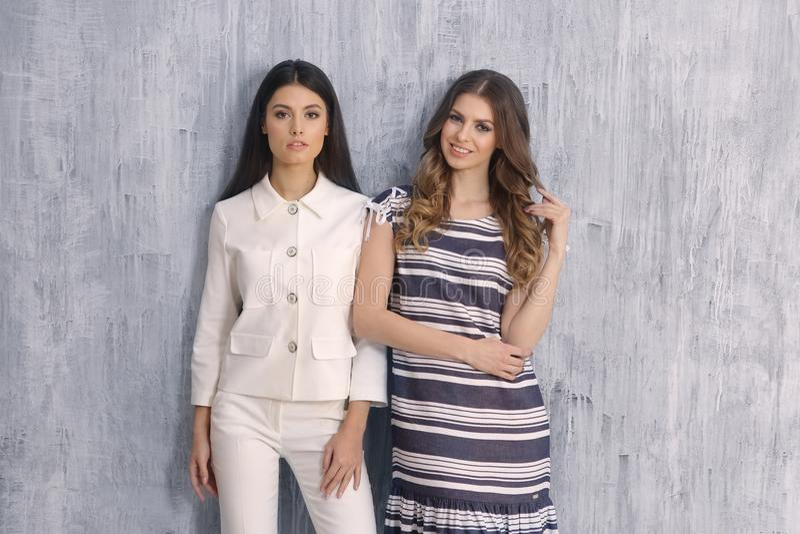Twee modelleren meisje in kostuum van de de kleren het witte broek van de de zomermanier en gestreepte korte kokerkleding stock afbeeldingen