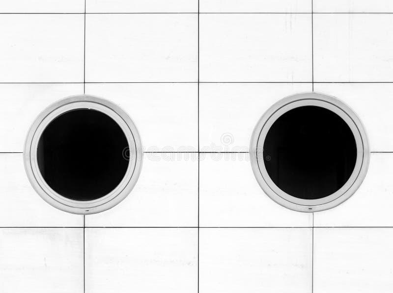Twee moderne ronde vensters op een witte betegelde muur stock fotografie