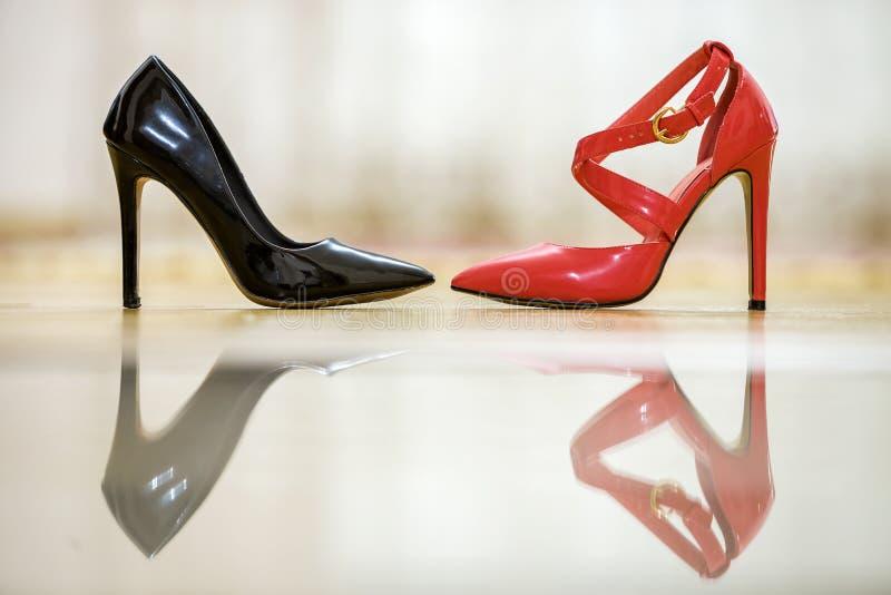 Twee modieuze comfortabele hoge vrouwelijke schoenen van het hielleer, rood en zwart, op lichte exemplaar ruimteachtergrond Stijl royalty-vrije stock foto