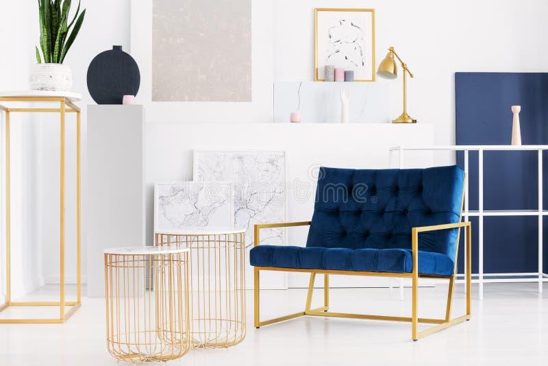 Twee modieuze lijsten naast benzine blauwe leunstoel in helder woonkamerbinnenland van moderne flat royalty-vrije stock foto