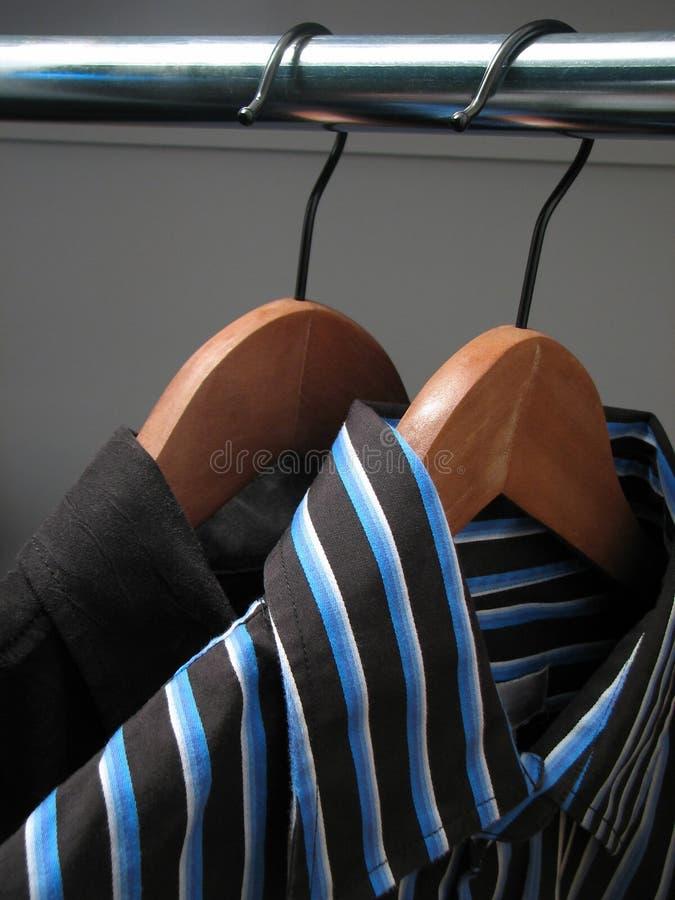 Twee modieuze overhemden op houten hangers royalty-vrije stock afbeelding