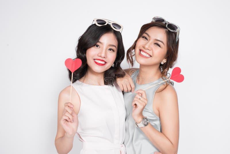 Twee modieuze vrouwen in aardige kleding zich en greep die verenigen stock afbeeldingen