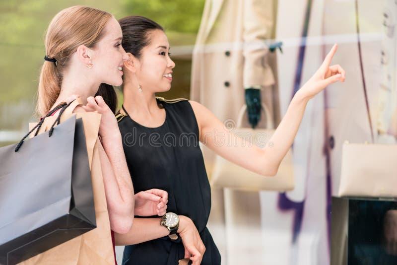 Twee modieuze vrouwen die document zakken dragen terwijl het winkelen in de zomer stock afbeeldingen