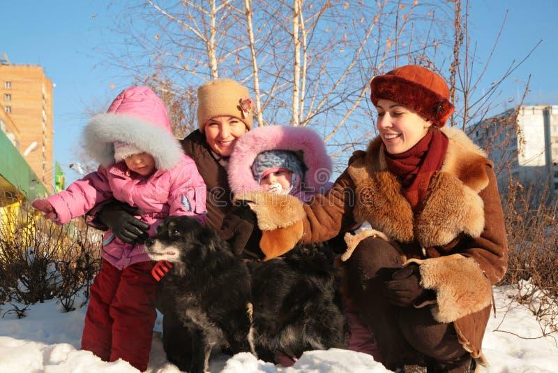 Twee moeders met kinderen en hond stock fotografie