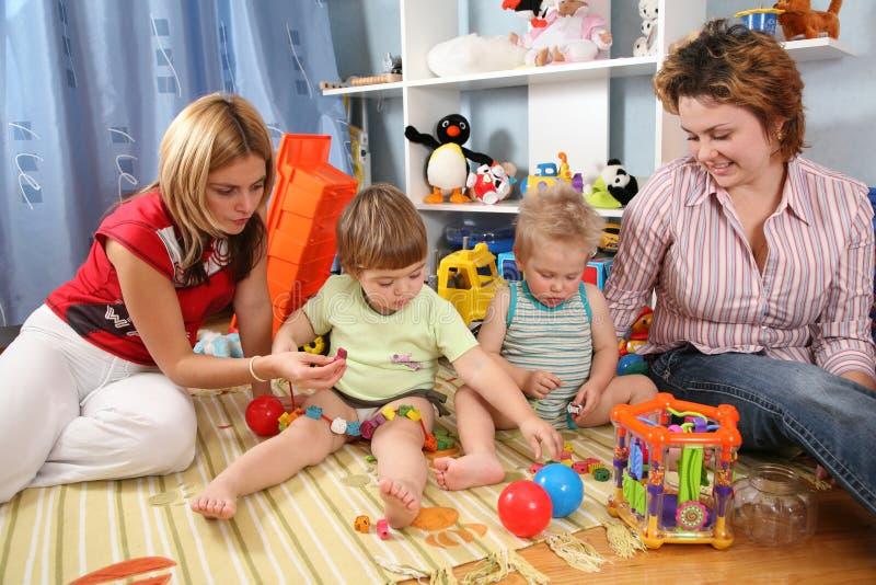 Twee moeders spelen met kinderen royalty-vrije stock afbeelding