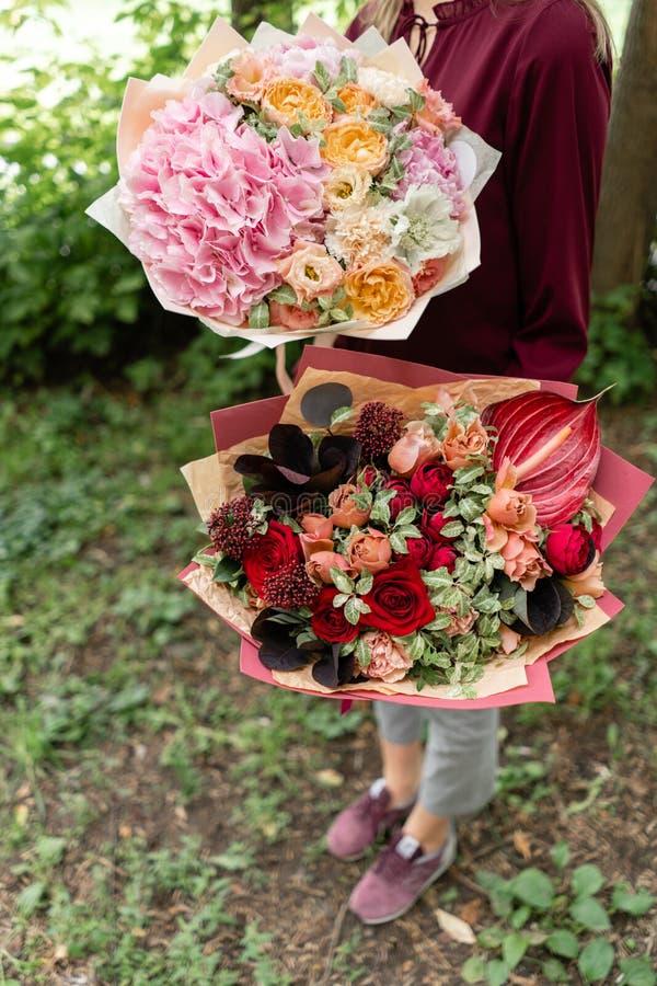 Twee Mooi de zomerboeket Regeling met mengelingsbloemen Jong meisje die rode en roze bloemstukken houden E royalty-vrije stock afbeeldingen