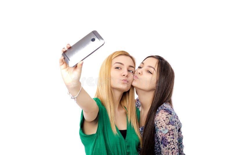 Twee mooi meisjesblonde en brunette die grappige selfie, kus nemen royalty-vrije stock afbeeldingen