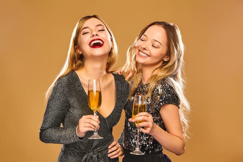 Twee mooie blonde meisjes die op gouden achtergrond stellen stock afbeeldingen