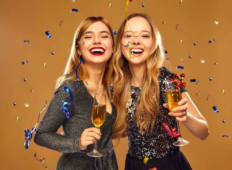 Twee mooie blonde meisjes die op gouden achtergrond stellen royalty-vrije stock fotografie