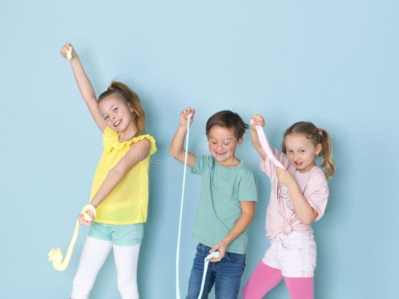 Twee mooie en grappige meisjes en één het koele jongen spelen met heel wat slijm voor blauwe achtergrond en het hebben van heel w stock afbeeldingen