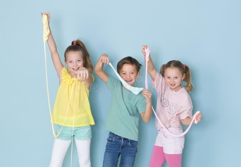 Twee mooie en grappige meisjes en één het koele jongen spelen met heel wat slijm voor blauwe achtergrond en het hebben van heel w royalty-vrije stock afbeelding