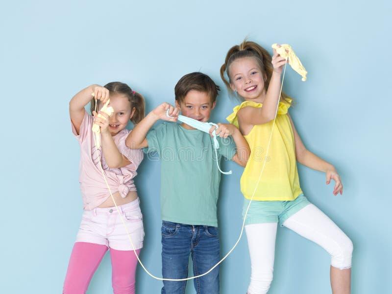 Twee mooie en grappige meisjes en één het koele jongen spelen met heel wat slijm voor blauwe achtergrond en het hebben van heel w stock afbeelding