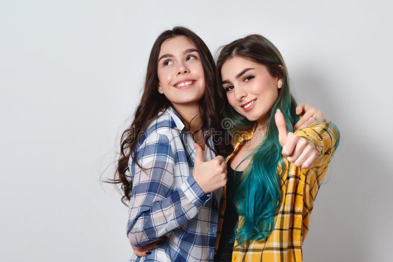 Twee mooie en meisjes die beduimelt omhoog glimlachen tonen Op witte achtergrond stock afbeeldingen