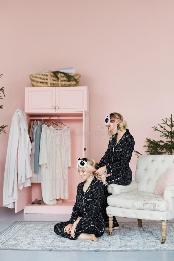 Twee mooie, gelukkige en glimlachende blonde modelmeisjes in modieuze pyjama's en in modieuze slaapmaskers in de vorm van stock foto's