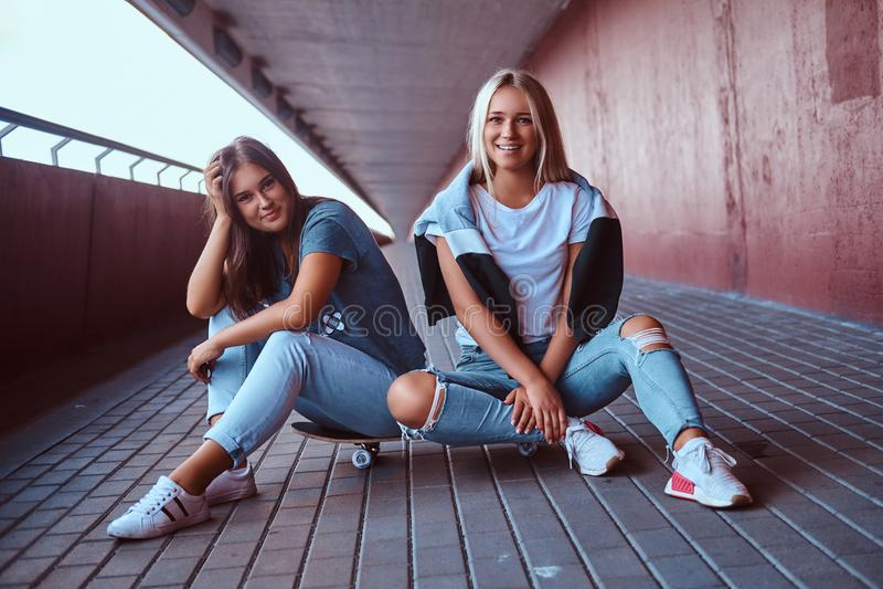 Twee mooie gelukkige hipstermeisjes die op skateboard bij een stoep onder brug zitten stock fotografie