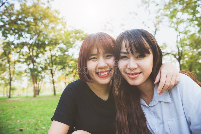 Twee mooie gelukkige jonge Aziatische vrouwenvrienden die pret hebben samen bij park en een selfie nemen stock afbeeldingen
