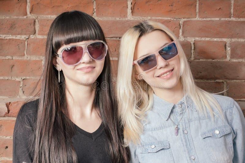 Twee mooie gelukkige meisjes in in zonnebril op de stedelijke achtergrond of de rode bakstenen muur Jonge hipstermensen In openlu stock foto