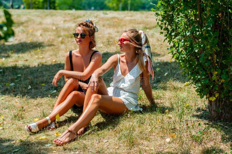 Twee mooie gelukkige vrouwen op gras het ontspannen in openlucht in de zomer stock afbeelding