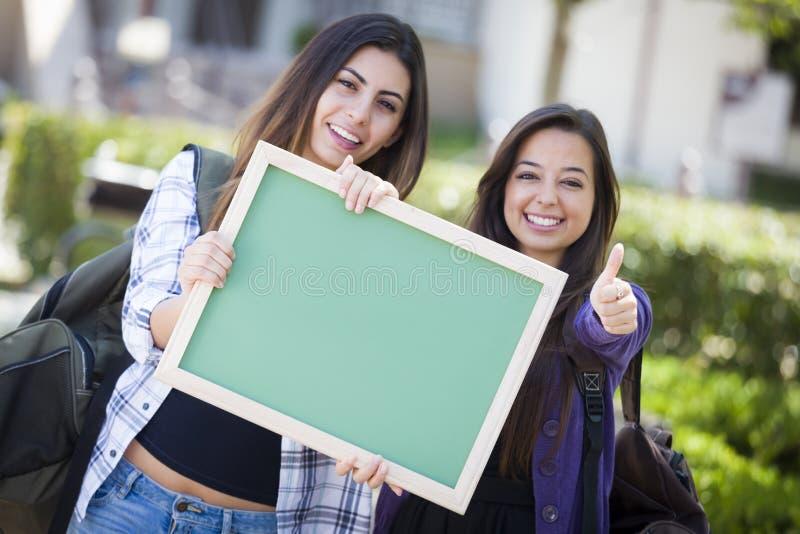 Twee Mooie Gemengde Ras Vrouwelijke Studenten met Duimen  royalty-vrije stock afbeelding