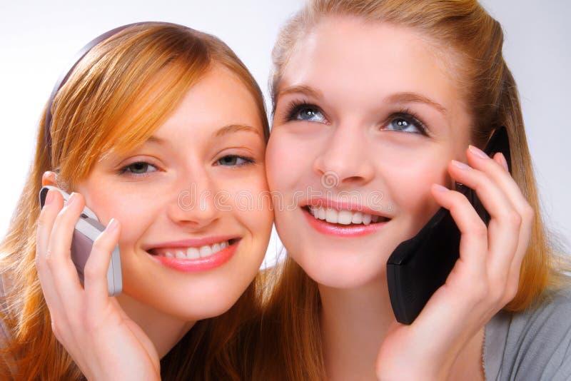 Twee mooie gilrs met mobiles stock afbeelding