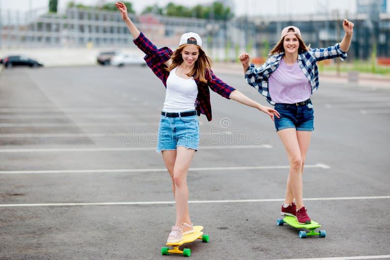 Twee mooie glimlachende blonde meisjes die geruite overhemden, kappen en denimborrels dragen longboarding op het lege parkeerterr stock afbeelding