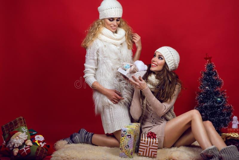 Twee mooie glimlachende meisjes die witte gebreide hoeden, sjaals en sweaters dragen die elkaar geven stelt bij Kerstboom voor stock foto's