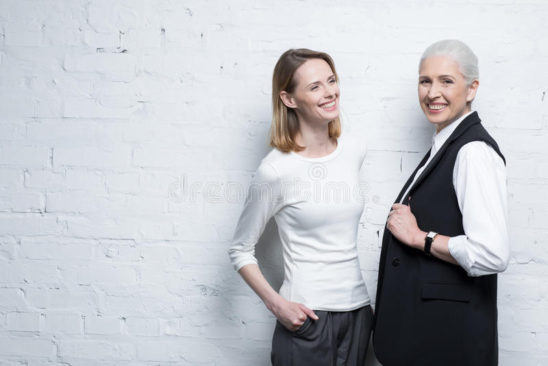 Twee mooie glimlachende vrouwen die zich verenigen royalty-vrije stock foto's