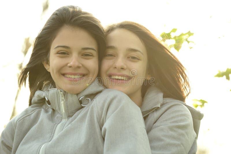 Twee mooie jonge en vrouwen die koesteren lachen royalty-vrije stock afbeeldingen