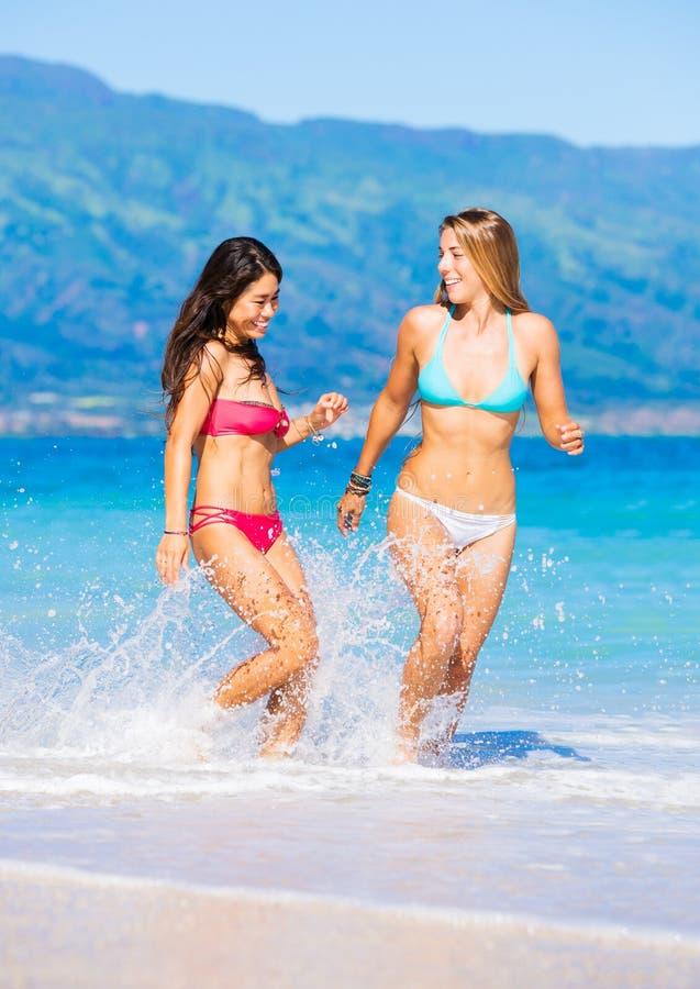 Een bed op het strand voor deze twee meiden