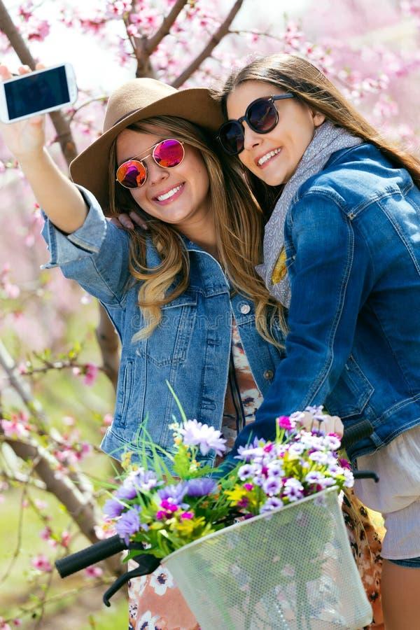 Twee mooie jonge vrouwen die een selfie op het gebied nemen stock afbeeldingen