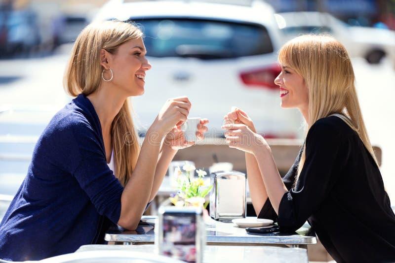 Twee mooie jonge vrouwen die en op een terras in de straat spreken lachen royalty-vrije stock foto's