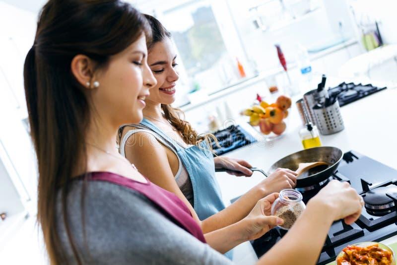 Twee mooie jonge vrouwen die en peper koken toevoegen aan groenten royalty-vrije stock afbeelding