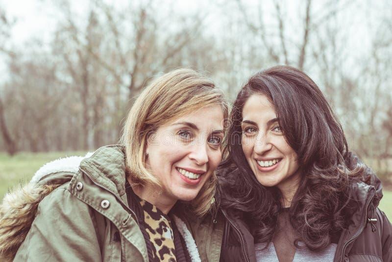 Twee mooie jonge vrouwen die, en pret in openlucht in een koude de herfstdag glimlachen hebben spreken Natuurlijk daglicht, natuu stock foto