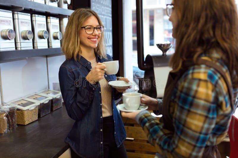 Twee mooie jonge vrouwen die koffie drinken en in een koffiewinkel spreken stock foto's