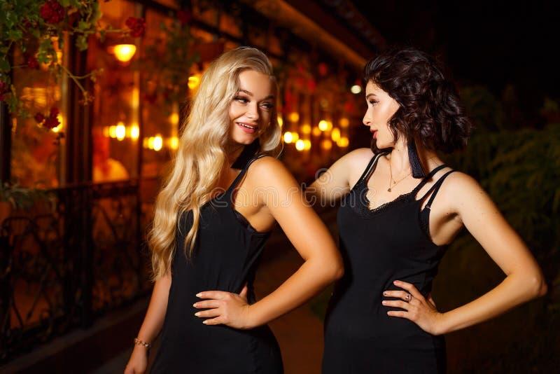 Twee mooie jonge vrouwen die op camera op de lichten van de nachtstad, het concept schoonheid en manier stellen royalty-vrije stock afbeeldingen
