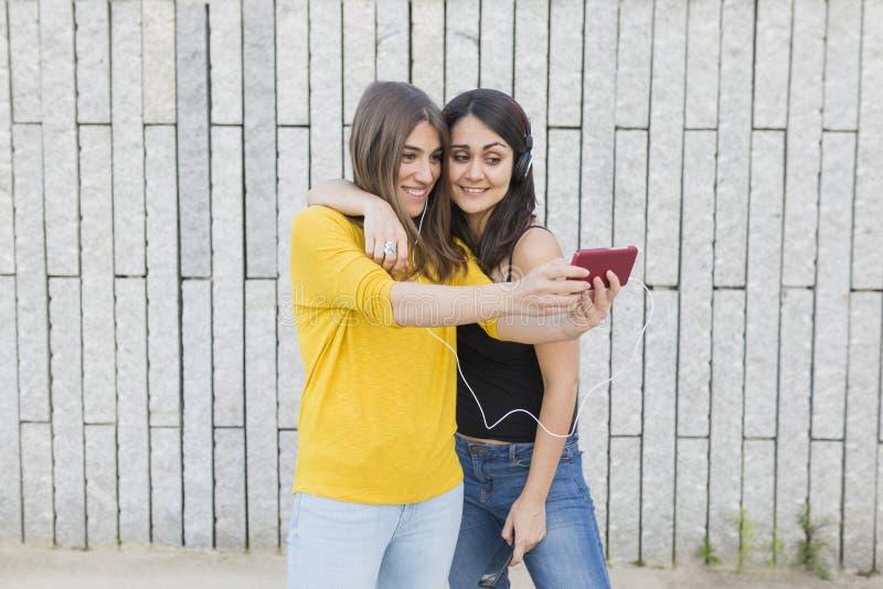 Twee mooie jonge vrouwen die pret hebben in openlucht Het nemen van een beeld met mobiele telefoon en het luisteren aan muziek To stock afbeeldingen