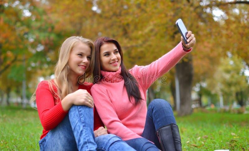 Twee mooie jonge vrouwen die selfie maken stock fotografie