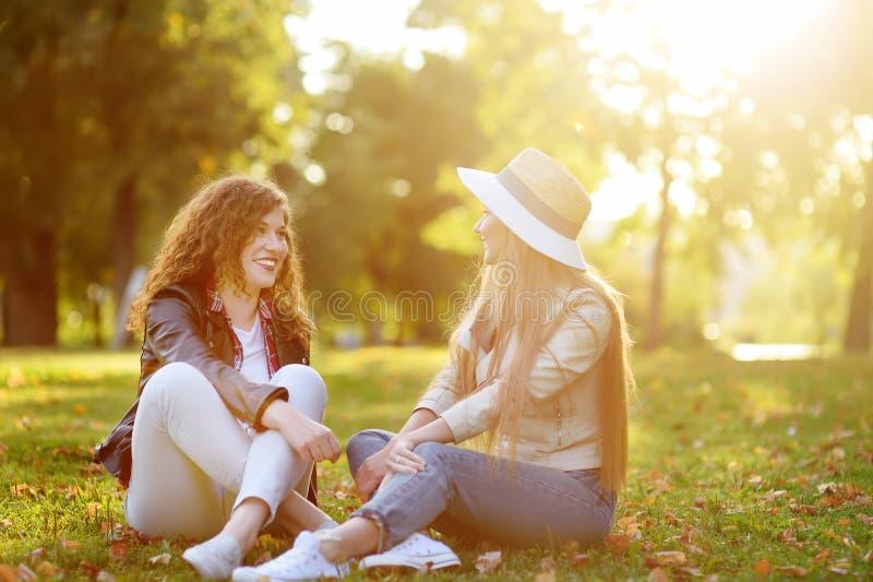 Twee mooie jonge vrouwen die terwijl het zitten op de grond bij zonnig park spreken Mededeling en roddel royalty-vrije stock foto