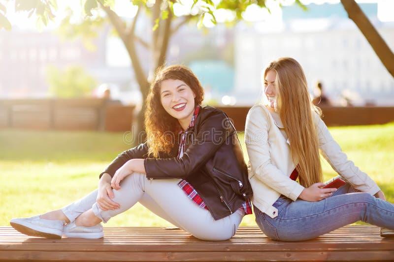 Twee mooie jonge vrouwen die terwijl het zitten op een bank bij zonnig park spreken stock afbeeldingen