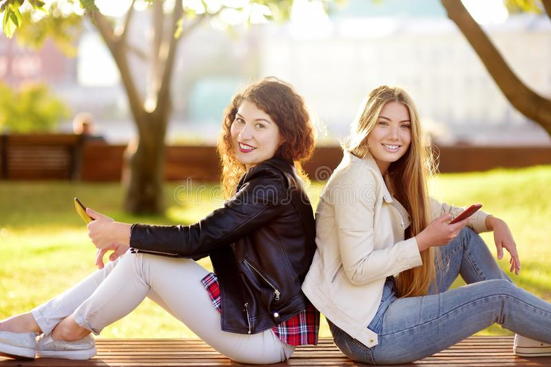 Twee mooie jonge vrouwen die terwijl het zitten op een bank bij zonnig park spreken stock afbeelding