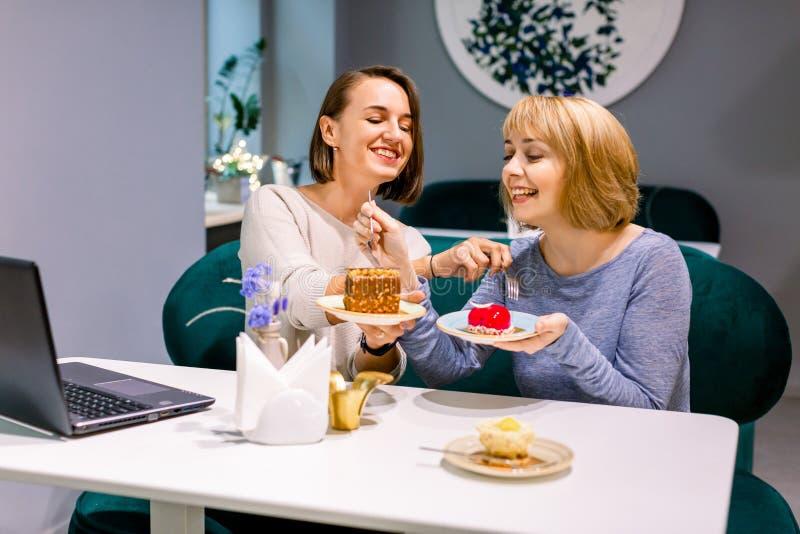 Twee mooie jonge vrouwen genieten van koffie en taart samen in een café dat aan een tafel zit te lachen en te roddelen met stock afbeeldingen