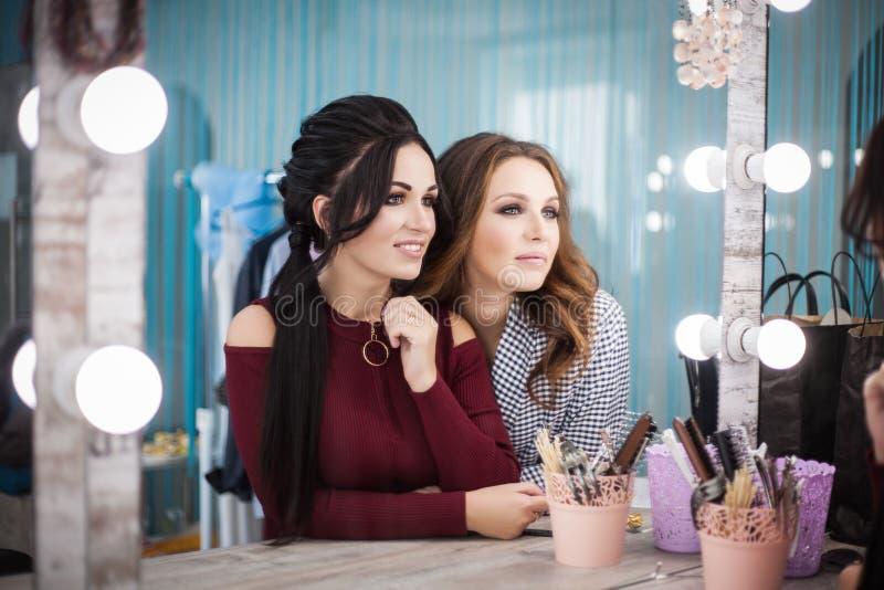 Twee mooie jonge vrouwen kijken in de spiegel in de schoonheidssalon Haar en make-up royalty-vrije stock fotografie