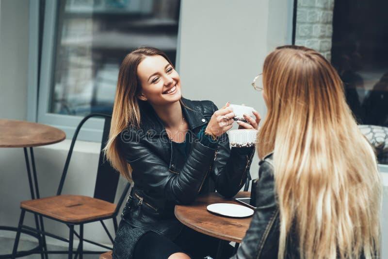 Twee mooie jonge vrouwen in manierkleren die rust het spreken en het drinken koffie in restaurant hebben openlucht royalty-vrije stock afbeelding