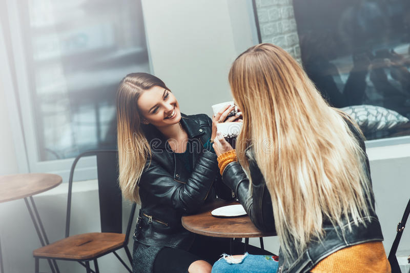 Twee mooie jonge vrouwen in manierkleren die rust het spreken en het drinken koffie in restaurant hebben openlucht royalty-vrije stock foto's