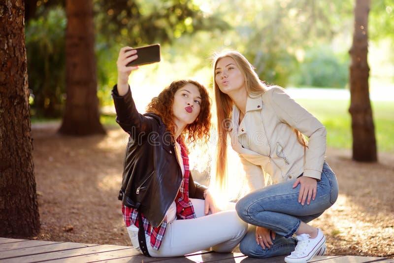 Twee mooie jonge vrouwen nemen selfie op zonnig park meisjes stock afbeelding