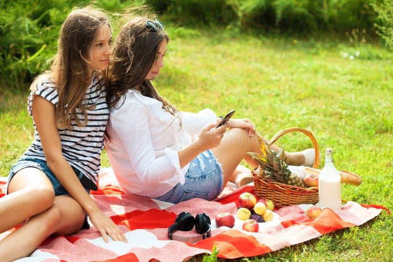 Twee mooie jonge vrouwen op een picknick die de het Exemplaarruimte van het smartphonescherm bekijken stock fotografie
